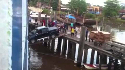 Car boarding ship over a wooden plank